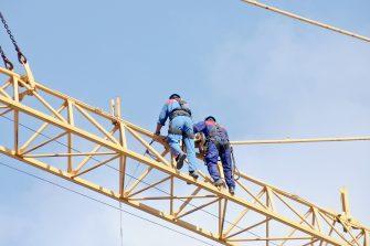 Men climbing yellow suspension